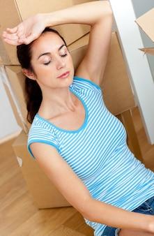 Uitgeputte spaanse vrouw die op de vloer met cardboards ligt