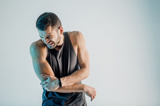 Uitgeputte sportman die pijn in elleboog voelt. jonge, bebaarde europese man draagt sportuniform. concept van sportblessure. geïsoleerd op turkooizen achtergrond. studio opname. ruimte kopiëren