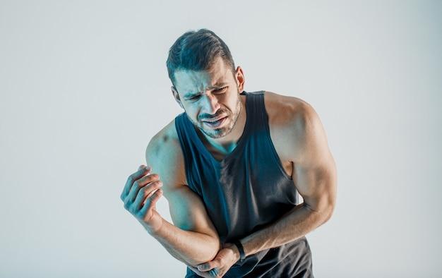 Uitgeputte sportman die pijn in elleboog voelt. jonge, bebaarde europese man draagt sportuniform. concept van sportblessure. geïsoleerd op turkooizen achtergrond. studio shoot