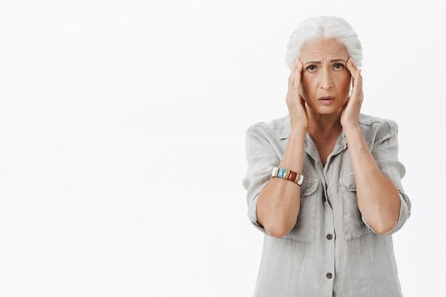 Uitgeputte trieste grootmoeder die haar hoofd aanraakt, klagende hoofdpijn heeft, migraine heeft