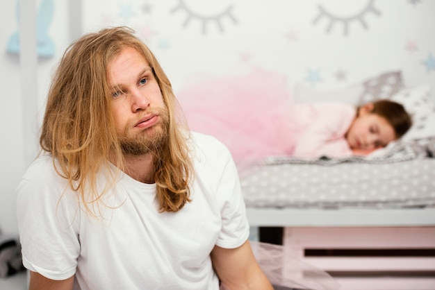 Uitgeputte vader naast slaperige dochter thuis