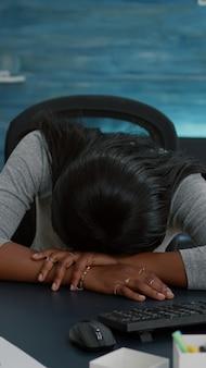 Uitgeputte vermoeide slaperige student die op bureaulijst in woonkamer slaapt