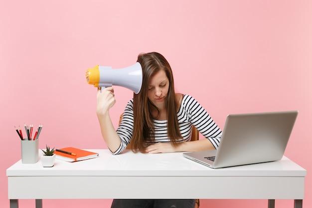 Uitgeputte vermoeide vrouw die op een megafoon leunt, zit en werkt aan een project aan een wit bureau op kantoor met een pc-laptop