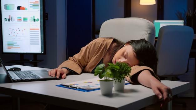 Uitgeputte vermoeide zakenvrouw slapend op bureautafel in opstartend kantoor