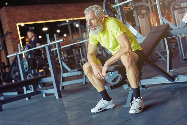 Uitgeputte volwassen man in sportkleding die rust na een zware training in de sportschool