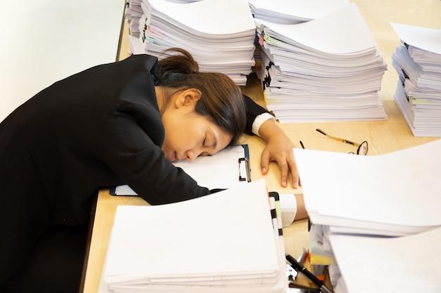 Uitgeputte vrouw heeft veel werk met documenten in slaap vallen op bureau.