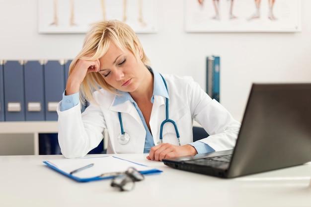 Uitgeputte vrouwelijke arts in bureau
