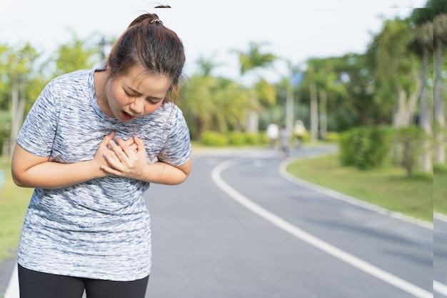 Uitgeputte vrouwelijke atleet die pijnlijke angina pectoris of astma-ademhalingsproblemen lijdt na hard trainen