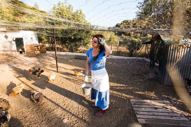 Uitgeputte vrouwelijke landbouwers voedende kip op het gebied