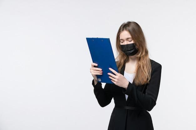 Uitgeputte vrouwelijke ondernemer in pak die haar medisch masker draagt en documenten opheft die lijden aan hoofdpijn op wit