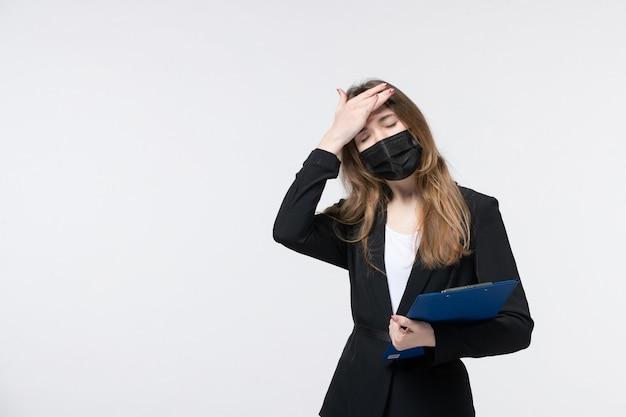 Uitgeputte vrouwelijke ondernemer in pak die haar medisch masker draagt en documenten vasthoudt die lijden aan hoofdpijn op wit