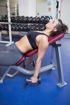 Uitgeputte vrouwentraining met gewichten