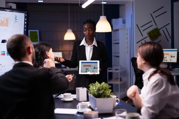 Uitgeputte workaholic afro-amerikaan die financiële grafieken toont met behulp van tabletoverbelasting in bedrijf o...
