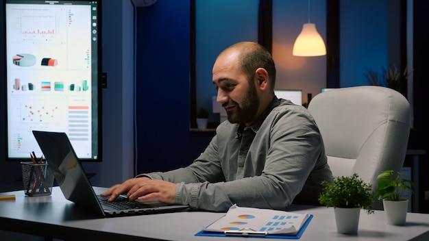 Uitgeputte zakenman die overwerkt op de deadline van het financiële bedrijf