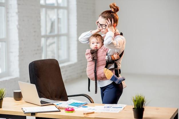 Uitgeputte zakenvrouw die haar hoofd vasthoudt terwijl ze met haar zoontje op kantoor staat tijdens het werk