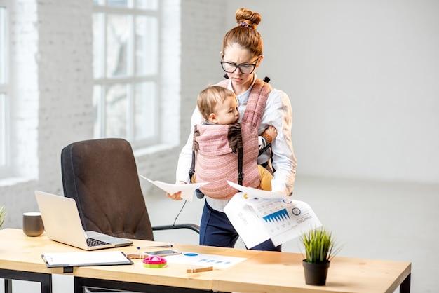 Uitgeputte zakenvrouw die werkt met papieren documenten met haar zoontje op kantoor