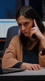 Uitgeputte zakenvrouw gebaren terwijl ze aan de telefoon praat over de marketingstrategie 's avonds laat in het opstartkantoor