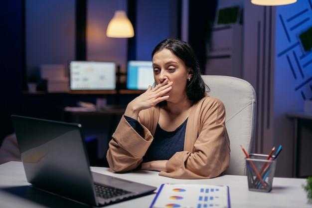 Uitgeputte zakenvrouw geeuwen die werkt aan een belangrijk project in een financieel bedrijf. slimme vrouw zit op haar werkplek in de loop van de late nachturen en doet haar werk.