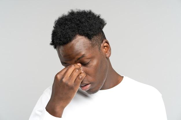 Uitgeputte zwarte man wil slapen wrijven in zijn ogen voelt moe na het werk op laptop overwerk