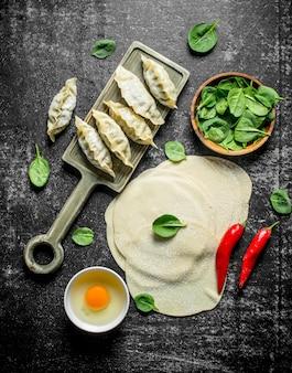 Uitgerold deeg voor het maken van zelfgemaakte rauwe gedza-dumplings op een donkere rustieke tafel