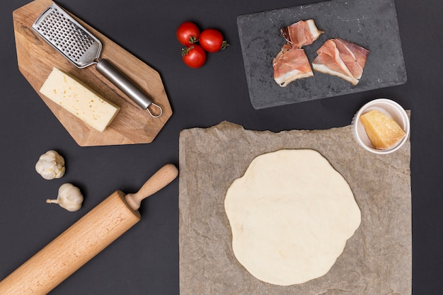 Uitgerold pizzadeeg; pizza-ingrediënt en rauw vlees met keukengerei over aanrecht