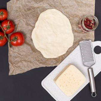Uitgerold pizzadeeg; tomaten; kaas en gedroogde rode chili met keukengerei op zwarte achtergrond