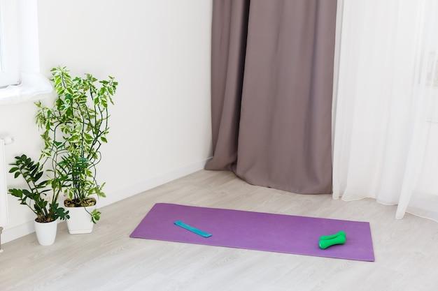 Uitgerolde yogamat op houten vloer in modern fitnesscentrum of thuis met grote ramen en witte bakstenen muren, comfortabele ruimte voor sportoefeningen, mediteren, yoga-apparatuur