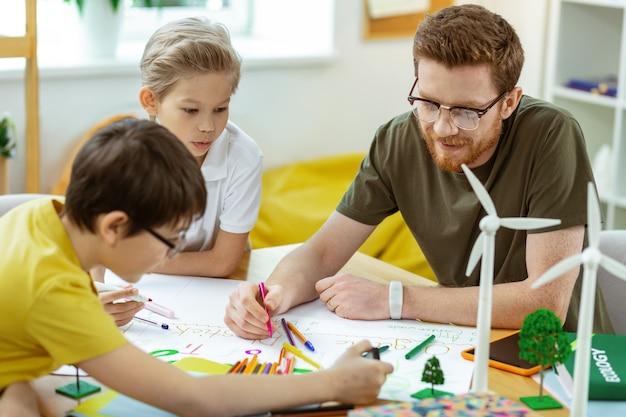 Uitgerust licht klaslokaal. gember knappe leraar met rode baard die op het papier schrijft met kleurrijke potloden en stiften