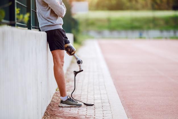 Uitgesneden foto van knappe kaukasische sportieve gehandicapte man in sportkleding en met kunstbeen leunend op hek terwijl armen gekruist.