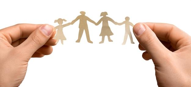 Uitgesneden papieren kettingfamilie met de bescherming van holle handen, concept voor veiligheid en zorg