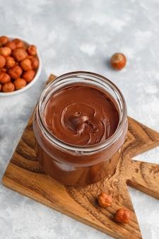 Uitgespreide chocolade of nogaroom met hazelnoten in glaskruik op beton, copyspace