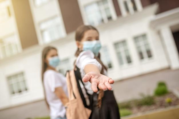 Uitgestrekte open palm van schoolmeisje dat met haar moeder met de hand naar school loopt die beschermende maskers draagt