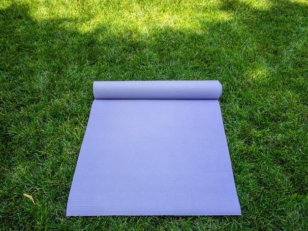 Uitgevouwen paarse yogamat of fitnessmat. yogamat of pilates in de schaduw op het groene gras