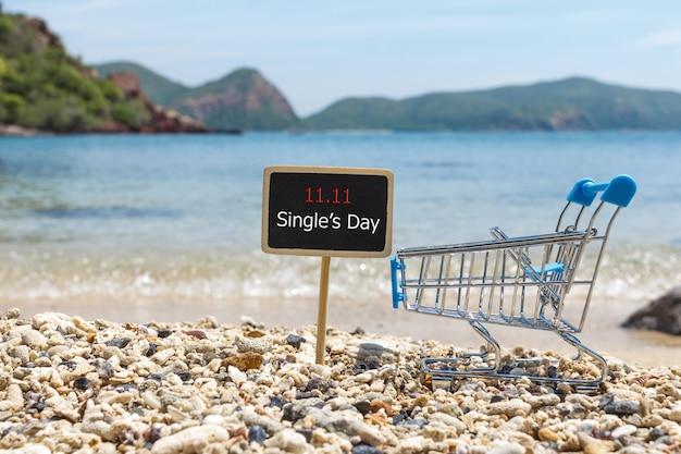 Uithangbord en winkelwagentje op het strand. online winkelen in china. verkoop concept voor één dag.