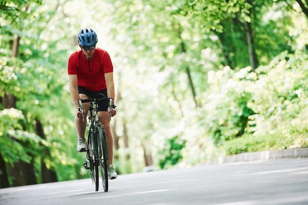 Uithoudingsvermogen test. fietser op een fiets is op de asfaltweg in het bos op zonnige dag