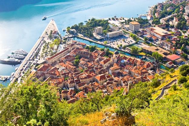 Uitkijkend over de baai van kotor in montenegro met uitzicht op bergen, boten en oude huizen met rode pannendaken