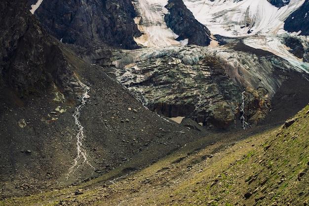 Uitlopers van gigantische gletsjer. verbazingwekkende rotsachtige reliëf met sneeuw en ijs. prachtige enorme berg rotsachtige natuurlijke muur met kleine watervallen. water uit gletsjer. fantastisch kunstwerk van majestueuze hooglandaard.