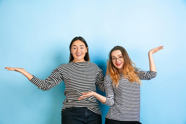 Uitnodigend, groet. jonge emotionele vrouwen die op gradiënt blauwe muur worden geïsoleerd. concept van menselijke emoties, gezichtsuitdrukking, vriendschap, advertentie. mooie kaukasische modellen in vrijetijdskleding.