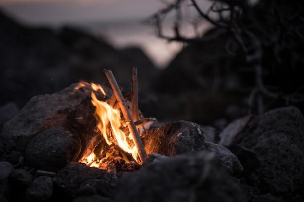 Uitnodigend kampvuur op het strand tijdens de zomer. voor de avond