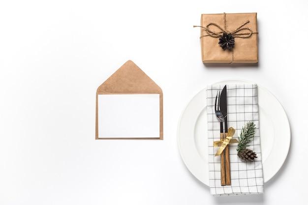 Uitnodiging voor kerstmis en nieuwjaar in envelop met kerstversiering op wit wordt geïsoleerd. plat lag wintervakantie concept.