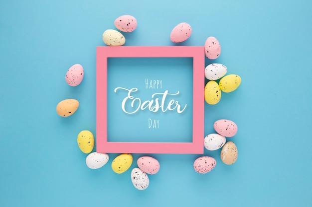 Uitnodiging voor pasen met eieren met een roze frame op een blauwe achtergrond