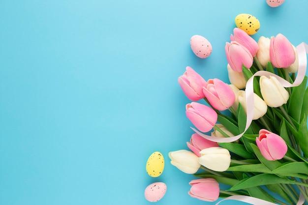 Uitnodiging voor pasen met tulpen op een blauwe achtergrond met kopie ruimte