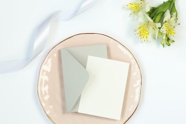 Uitnodigingskaart, bloemen, grijze envelop en lint op wit