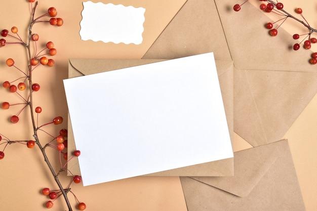 Uitnodigingssjabloon met enveloppen op een beige achtergrond met een herfsttak van een appelboom.