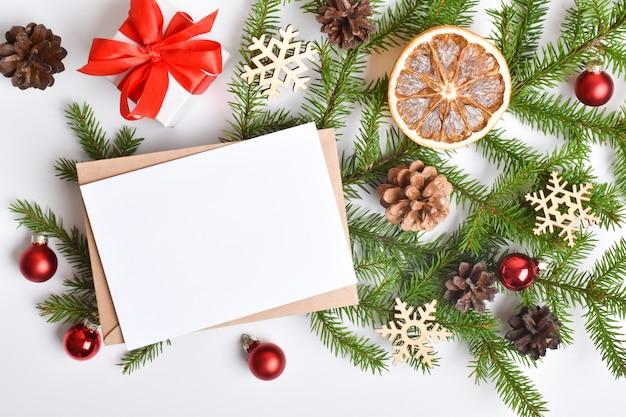 Uitnodigingssjabloon voor kerstmis en nieuwjaar. een kerstkaart met een envelop en een tak van een dennenboom, sinaasappels en kerstspeelgoed op een witte achtergrond. platte lay-out, bovenaanzicht, een plek om te kopiëren.