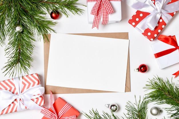 Uitnodigingssjabloon voor kerstmis en nieuwjaar. een kerstkaart met een envelop en geschenken. platte lay-out, bovenaanzicht, een plek om te kopiëren.