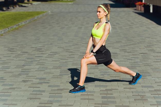 Uitrekken. vrouwelijke loper, atleet training buitenshuis. professionele hardloper, jogger die op straat traint. concept van gezonde levensstijl, sport, wellness, welzijn, beweging en actie, activiteit.