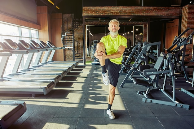 Uitrekkend lichaamsportret van een atletische man van middelbare leeftijd in sportkleding die aan het opwarmen is voordat hij gaat trainen in een