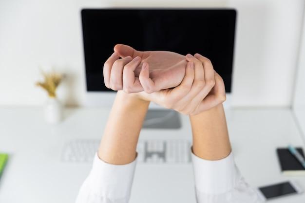 Uitrekkende armen in schaarse kantoorwerkplek. handen van een werknemer voor moderne desktop, overwerk en vermoeidheid concept