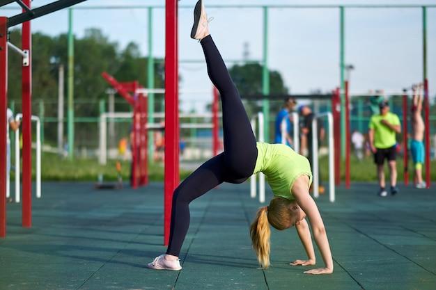 Uitrekkende danser of turnervrouw opleiding in de grond van trainingsporten